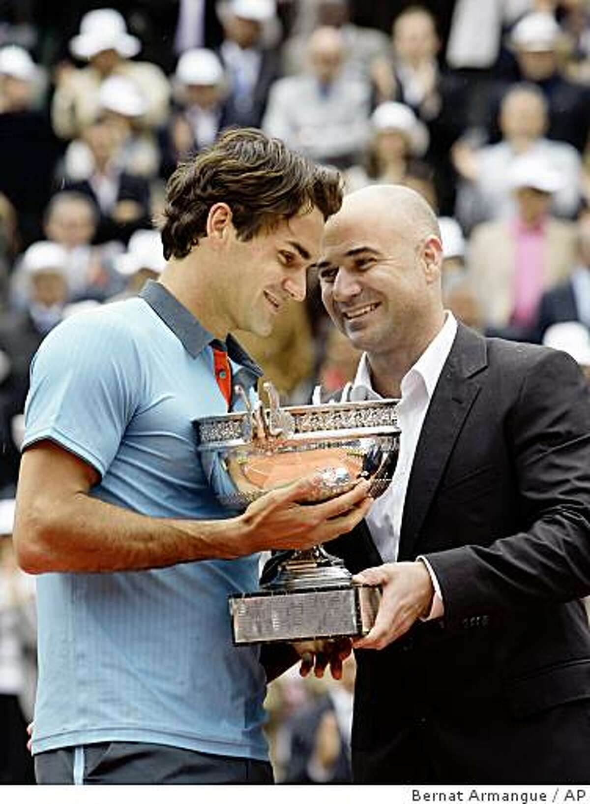Switzerland's Roger Federer, left, receives the trophy from tennis legend Andre Agassi after defeating Sweden's Robin Soderling during their men's singles final match of the French Open tennis tournament at the Roland Garros stadium in Paris, Sunday June 7, 2009. The victory gives Federer 14 Grand Slams, tying his career wins to American Pete Sampras. (AP Photo/Bernat Armangue)