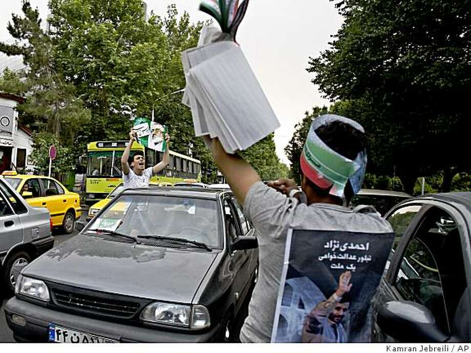 A young supporter of Iranian hard line president Mahmoud Ahmadinejad,  with his picture on his back, confronts a reformist candidate supporter of Mir Hussein Mousavi, left, among the traffic in downtown Tehran, Sunday, June 7, 2009. Iranian media says the main challenger to President Mahmoud Ahmadinejad is warning that Ahmadinejad may be trying to incriminate his supporters ahead of Friday's presidential election. (AP Photo / Kamran Jebreili) Photo: Kamran Jebreili, AP