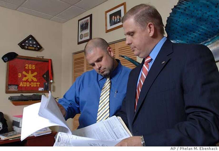 Ritch Workman, right, president of the Florida Association of Mortgage Brokers and co-owner of Workman Mortgage Co., goes over a client's mortgage application with his brother and co-owner, Robb Workman, in their offices in Melbourne, Fla., Monday, Jan. 14, 2008. Workman is working weekends and holidays as state and federal regulators attempt to tighten regulations on the industry and potentially restrict a lucrative source of income. (AP Photo/Phelan M. Ebenhack) Photo: Phelan M. Ebenhack