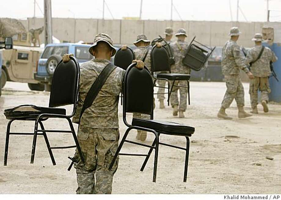 Paratroopers with the 3rd Brigade Combat Team, 82nd Airborne Division carry chairs after they handed over  their base in central  Baghdad, Iraq,  to the Iraqi security forces Friday, May 22, 2009. Under an agreement with Iraqi government, all US combat troops must leave Iraqi cities for garrisons outside the towns by the June 30 2009. (AP Photo/Khalid Mohammed) Photo: Khalid Mohammed, AP
