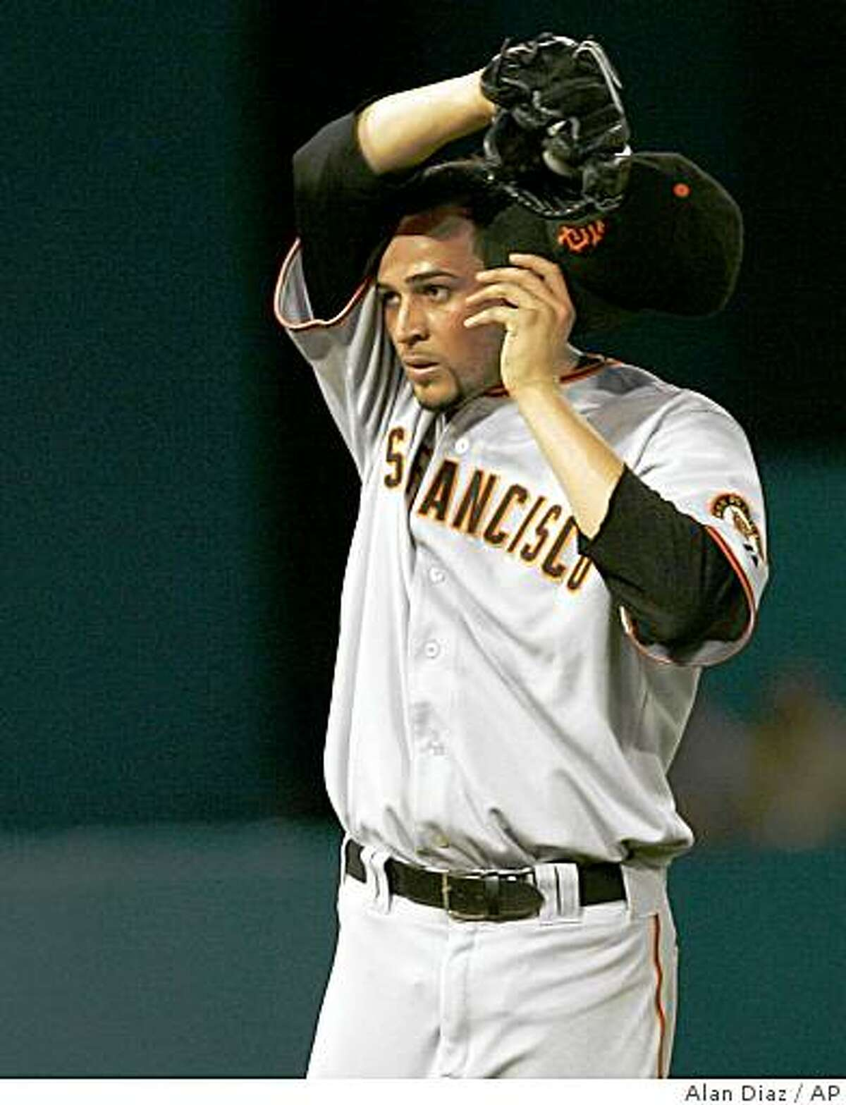 San Francisco Giants' pitcher Jonathan O. Sanchez wipes his face after Florida Marlins' Hanley Ramirez doubled in the third inning in Miami on Saturday.