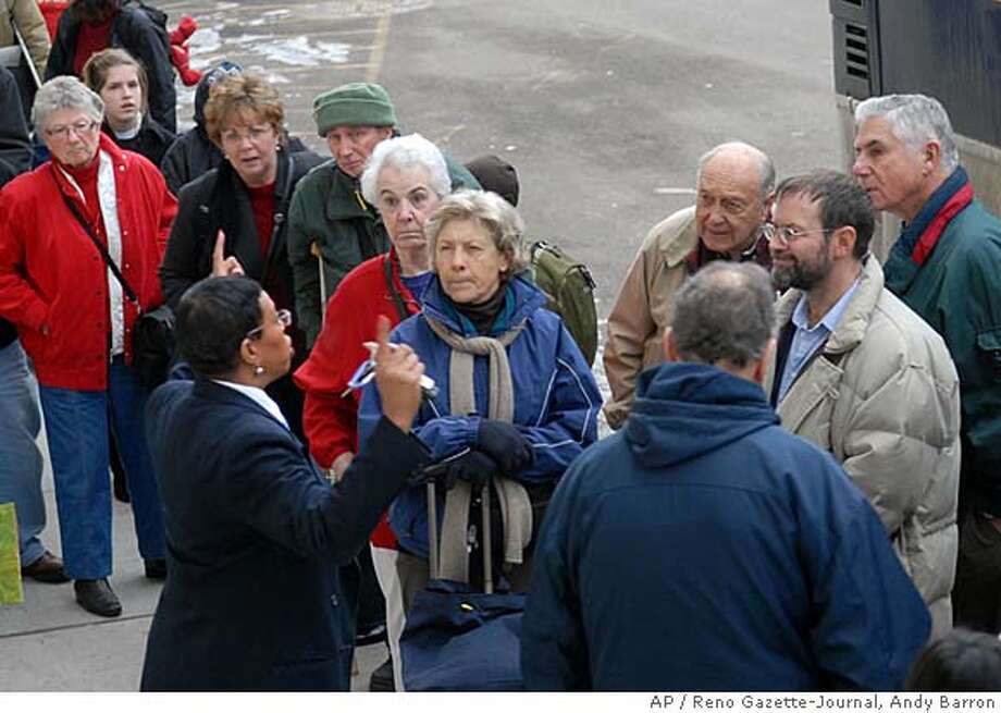 Amtrak ticket agent Janice Montgomery explains the bussing situation to the travelers Saturday, Feb. 2, 2008, from the stranded westbound train that was pulled back to Reno on Friday night. Passengers had to spend the night in hotels room in Reno. (AP Photo/Reno Gazette-Journal, Andy Barron) ** NEVADA APPEAL OUT, MAGS OUT, NO SALES ** Photo: Andy Barron