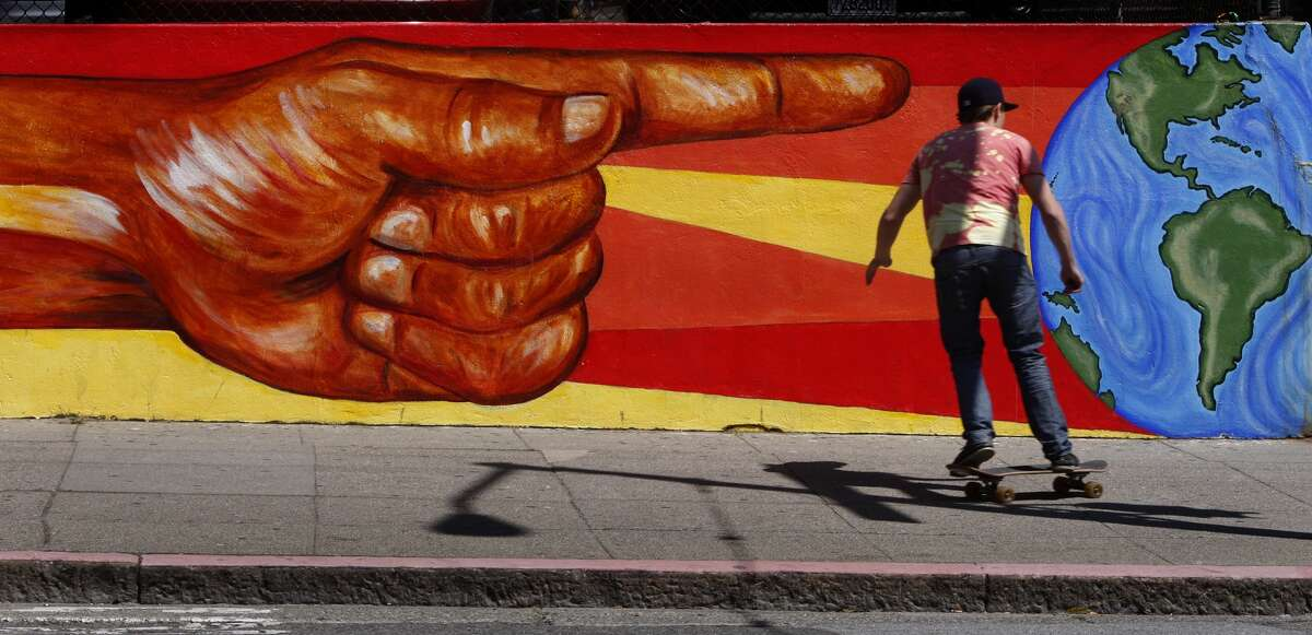 A skateboarder rolls past a mural at a CCSF campus at Hayes Street and Masonic Avenue in the Nopa neighborhood in San Francisco, Calif., on Thursday, May 21, 2009.