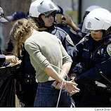 San Francisco Police officers remove personal items from a female protestor on Grove Street in San Francisco Tuesday, May 26, 2009. Demonstrators took part in a civil disobedience demonstration that blocked traffic for several hours on Van Ness Ave following the California Supreme Courts decision upholding of Prop 8 vote, to ban on gay marriage.