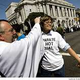 Bishop Rusty Clyma prays for Debra Walker from San Francisco prior to to arrest for blocking Van Ness ave at Grove streets in San Francisco Tuesday, May 26, 2009.