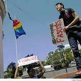 Danielli Speights (left) of San Francisco and Jacob Roger Sperber of San Francisco hold signs protesting the Supreme Court decision on Prop 8 handed down earlier in the day at  Market and Castro streets in  San Francisco.