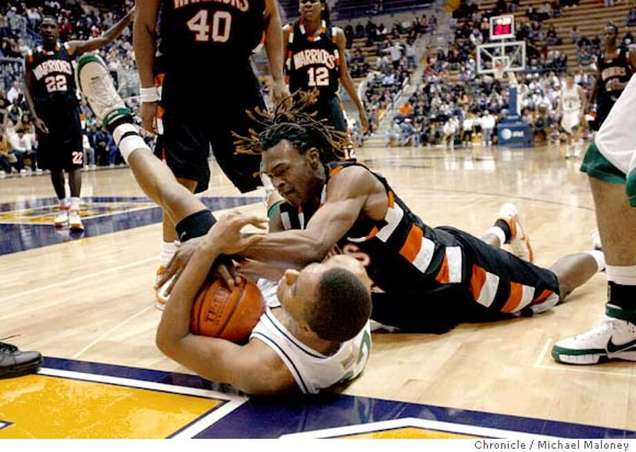 McClymonds Warriors Damon Powell (top) and De La Salle Spartans Brandon Thomas battle for a 2nd half loose ball.  The McClymonds Warriors of Oakland faced the De La Salle Spartans of Concord in a high school basketball game at the 11th annual Martin Luther King Holiday Classic at Haas Pavilion at UC Berkeley, CA on January 21. 2008. The McClymonds Warriors won 44-42.  Photo by Michael Maloney / The Chronicle Ran on: 01-22-2008  McClymonds' Damon Powell gets on top of De La Salle's Brandon Thomas in a scramble for the ball. Powell scored 10 points. Photo: Michael Maloney