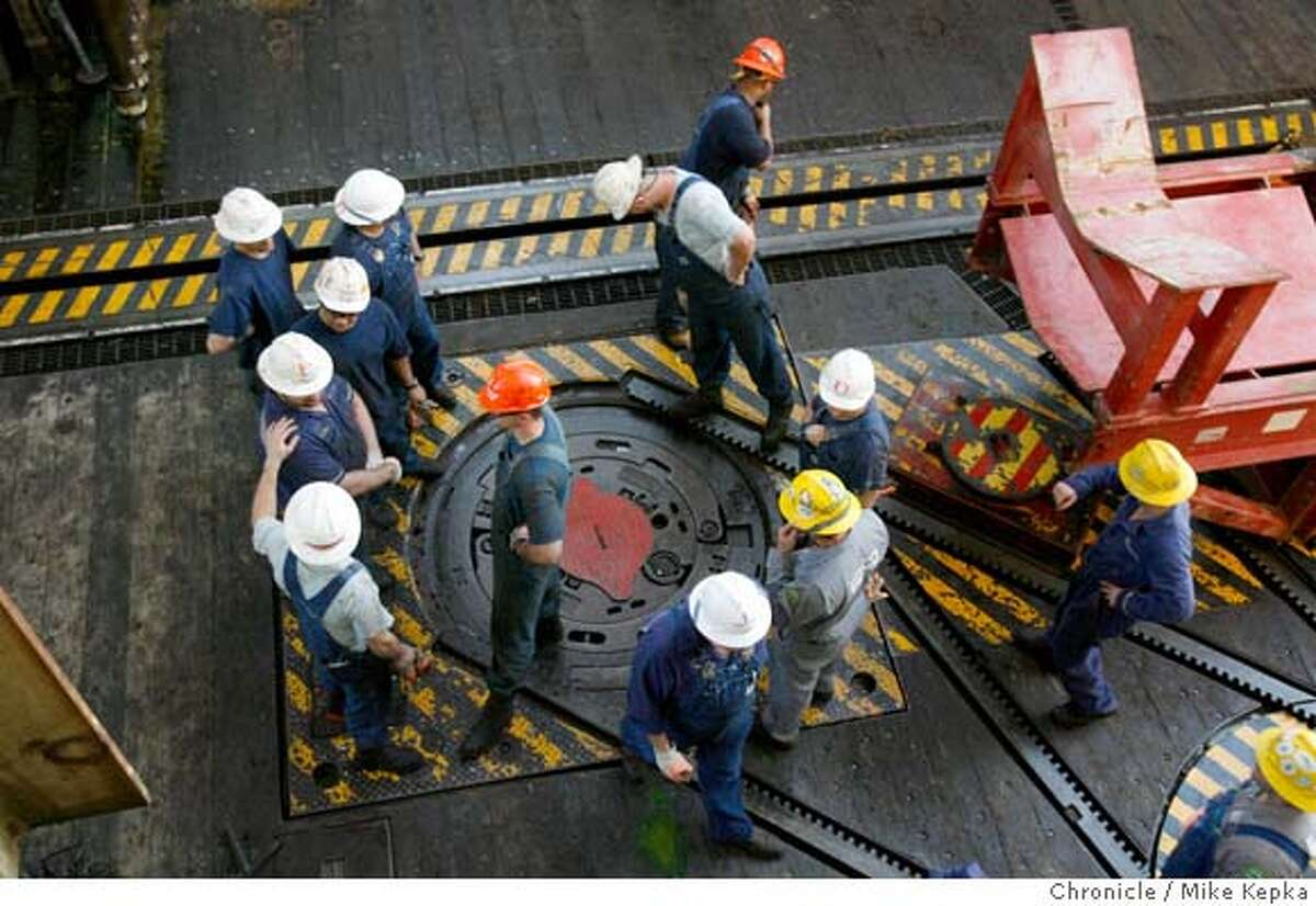 gulf0155_mk.JPG A group of roughnecks and their managers discuss safety and procedure as they are about to begin drilling on the ocean floor thousands of feet below the water's surface. Despite millions of dollars in damage from Hurricane Katrina, Chevron is spending billions drilling new oil wells in the Gulf of Mexico. We investigate their newest project 140 miles off the coast of Louisiana on a drilling ship called the Deep Sea Discovery. . 2/20/06 Mike Kepka / The San Francisco ChronicleRan on: 03-19-2006 Jay Darder, environment safety and compliance engineer for Chevron, surveys the scene from an elevated walkup on Discoverer Deep Seas.Ran on: 03-19-2006 Jay Darder, environment safety and compliance engineer for Chevron, surveys the scene from an elevated walkup on Discoverer Deep Seas.