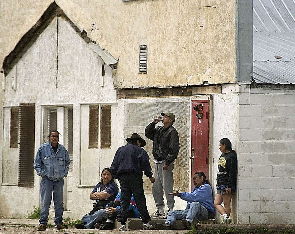 This June 7, 2003 file photo shows a man drinking a beer standing with other Native Americans on the streets of Whiteclay, Neb.The Oglala Sioux Tribe announced Thursday, Feb. 6, 2012, that it will file a $500 million federal lawsuit against some of the nation's largest beer distributors, alleging that they knowingly contributed to the chronic alcoholism, health problems and other social ills on the Pine Ridge Indian Reservation. The lawsuit also targets the four beer stores in Whiteclay, a Nebraska town (pop. 11) on the South Dakota border that sells about 5 million cans of beer per year.