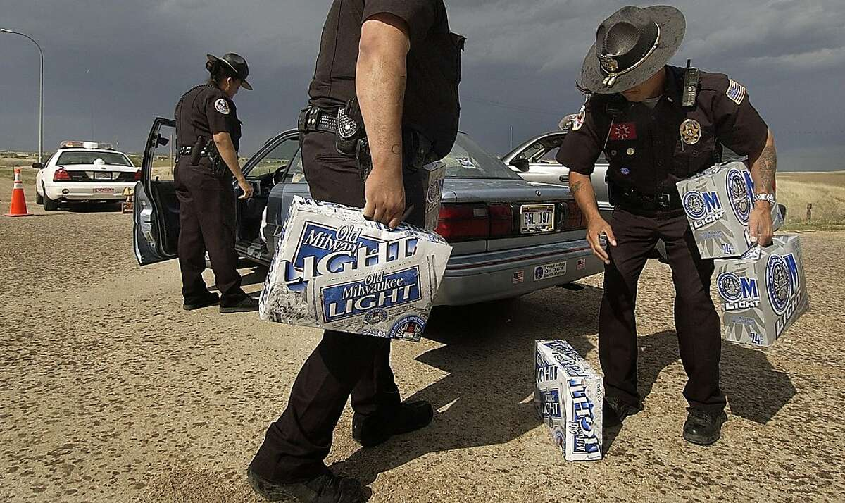 In this June 3, 2004 file photo, Pine Ridge police officers Mirian Laybad, left, Sgt. Oscar Hudspeth, center, and Lt. Mitch Wisecarver confiscate cases of beer at a checkpoint just north of Whiteclay, Neb. The Oglala Sioux Tribe announced Thursday, Feb. 6, 2012, that it will file a $500 million federal lawsuit against some of the nation's largest beer distributors, alleging that they knowingly contributed to the chronic alcoholism, health problems and other social ills on the Pine Ridge Indian Reservation. The lawsuit also targets the four beer stores in Whiteclay, a Nebraska town (pop. 11) on the South Dakota border that sells about 5 million cans of beer per year.