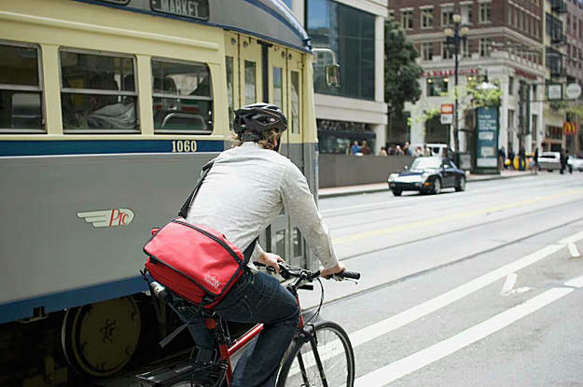 A cyclist shares the road with a Muni train in San Francisco.
