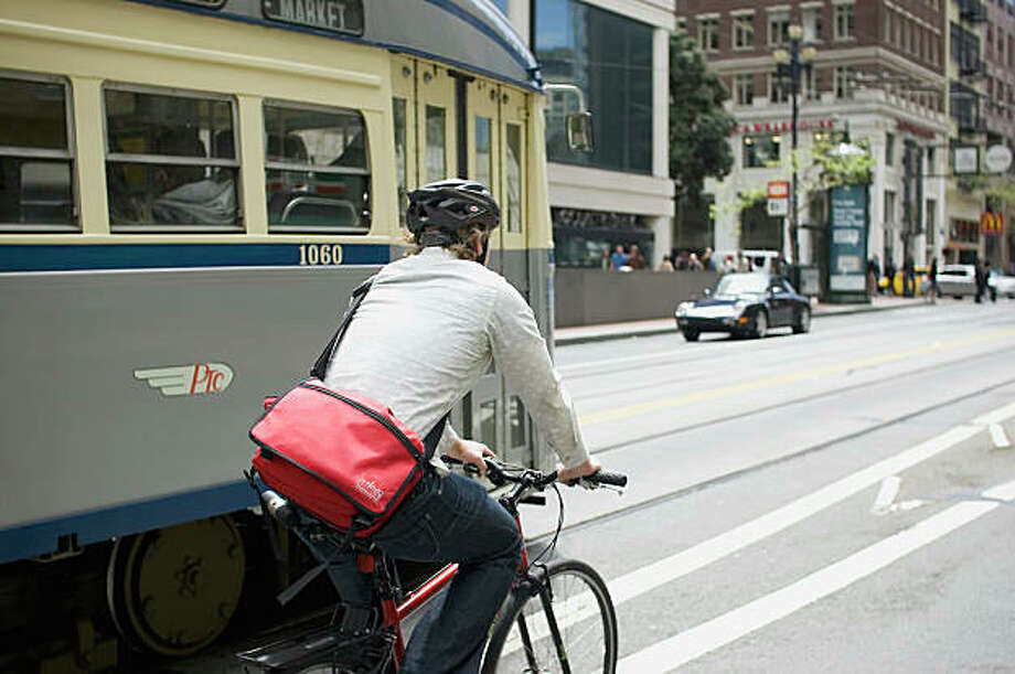 A cyclist shares the road with a Muni train in San Francisco. Photo: Dustin  Jensen