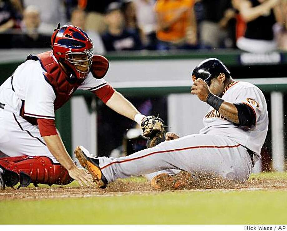 San Francisco Giants' Pablo Sandoval, right, is safe at home on a double by Juan Uribe as Washington Nationals catcher Josh Bard is late with the tag during the sixth inning of a baseball game Tuesday, June 2, 2009, in Washington. The Nationals won 10-6. (AP Photo/Nick Wass) Photo: Nick Wass, AP