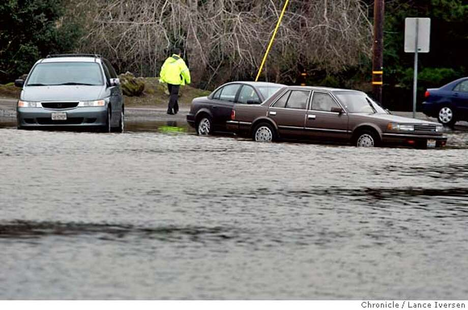 A Petaluma Police Officer walks past a group of stranded cars that were trapped Friday night on Stony Point Road when the area flooded. The water levels continue to drop after messy and very wet storm that seemed to hover over the Bay Area has moved east. Another weather front is expected to hit the Bay Area sometime late Saturday night. By Lance Iversen/The Chronicle Photo: Lance Iversen