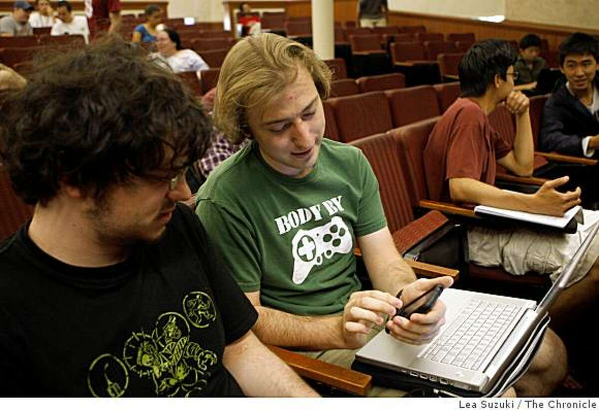 David Jacobs (second from left), first years PhD student discusses his class project on his iPhone to student Abe Davis, Stanford junior (left) before the start of the iPhone applications programming class at Stanford, Calif. on Monday May 18, 2009.