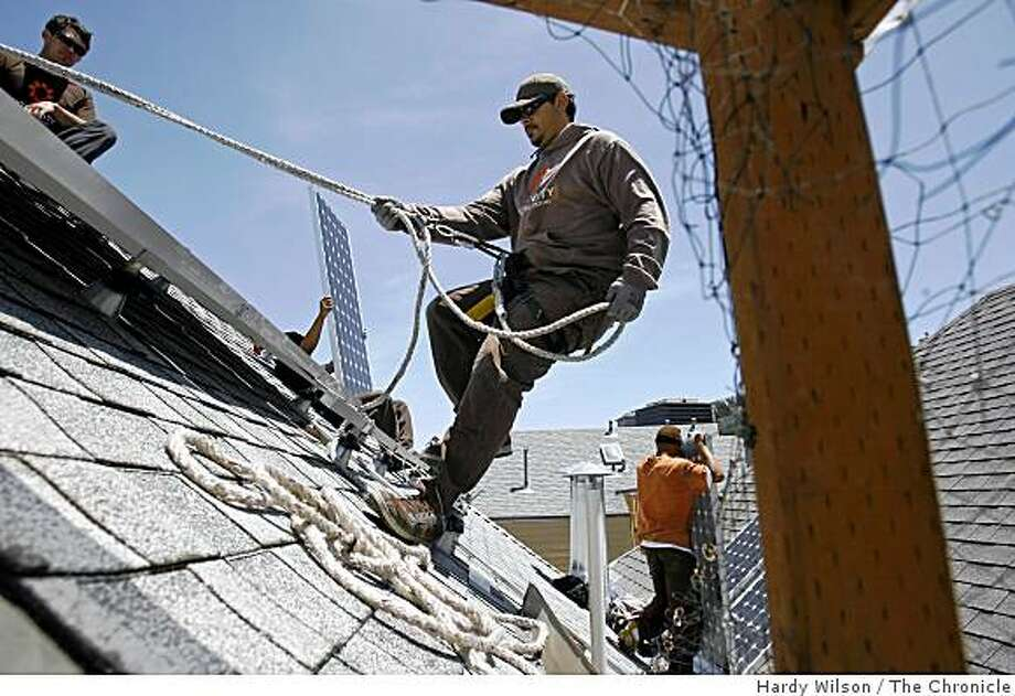 Francois Hunter, center, a crew leader for Sungevity, helps install solar panels with Jeremiah Eanes, left, Larry Galbert, second from left, and Lionel Gant, right, on a home at 1236 6th Avenue in San Francisco, Calif., on Thursday, May 14, 2009. Sungevity, which is based out of Berkeley, Calif., installs solar panels on local homes and uses Microsoft Virtual Earth to calculate how to install them and what they will cost. Photo: Hardy Wilson, The Chronicle