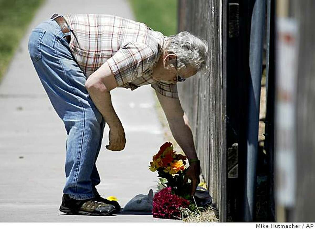 Thomas Dyke lays flowers at the gated entrance of Women's Health care Services Sunday, May 31, 2009, following the shooting death of abortion provider George Tiller at church in Wichita, Kan. (AP Photo/The Wichita Eagle, Mike Hutmacher, File) **NO MAGS NO SALES**