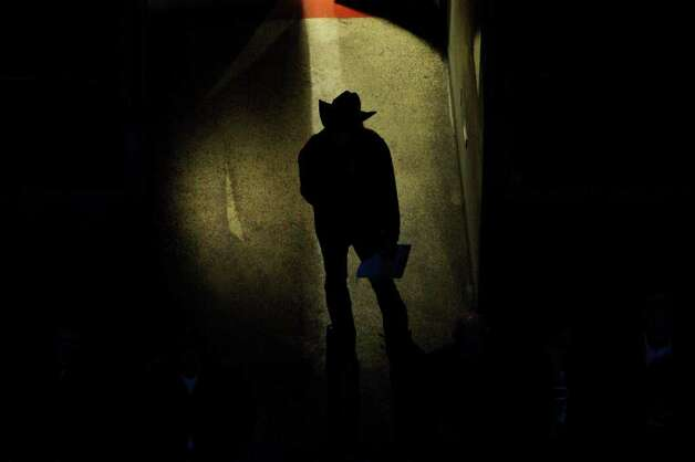 A rodeo fan watches the grand entry during the San Antonio Stock Show & Rodeo Thursday, Feb. 9, 2012 at the AT&T Center. Photo: EDWARD A. ORNELAS, San Antonio Express-News / © SAN ANTONIO EXPRESS-NEWS (NFS)