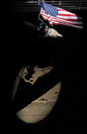 Kristen Bettis presents the American flag during the grand entry at the San Antonio Stock Show & Rodeo on Thursday, Feb. 9, 2012 at the AT&T Center. Photo: EDWARD A. ORNELAS, San Antonio Express-News / © SAN ANTONIO EXPRESS-NEWS (NFS)