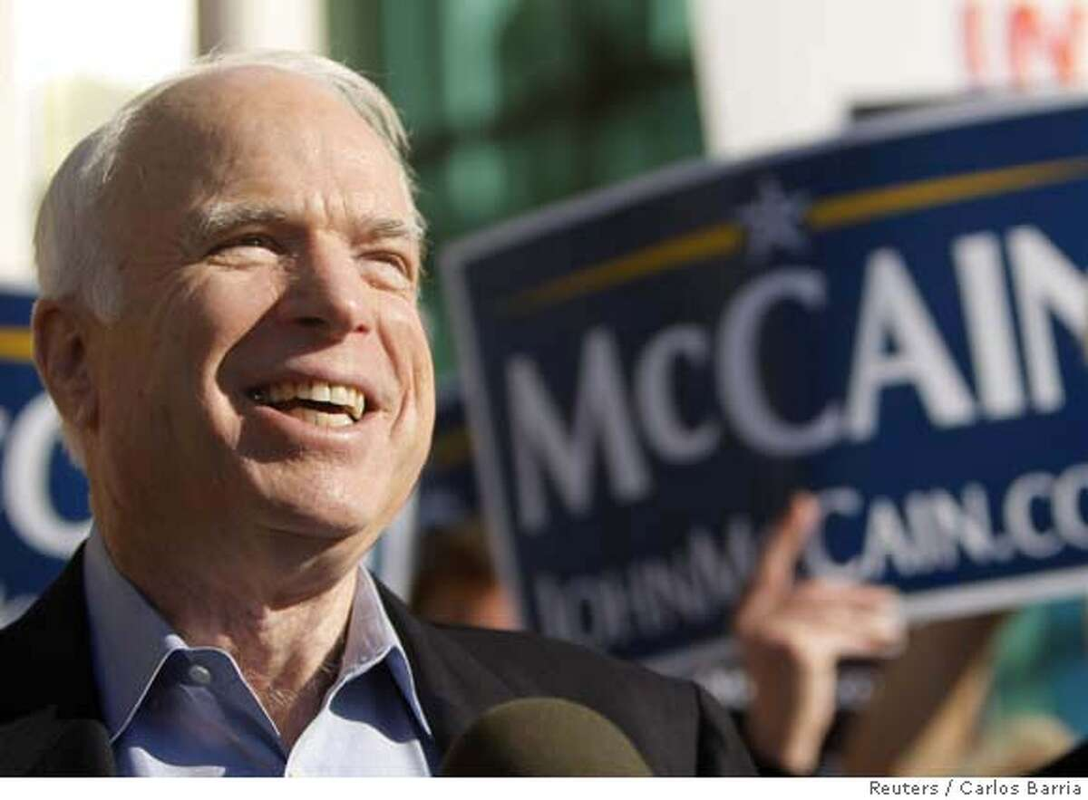 Republican presidential candidate U.S. Senator John McCain (R-AZ) smiles as he talks with media during a visit to a polling station in St. Petersburg, Florida January 29, 2008, the day of the Florida primary. REUTERS/Carlos Barria (UNITED STATES) US PRESIDENTIAL ELECTION CAMPAIGN 2008 (USA)