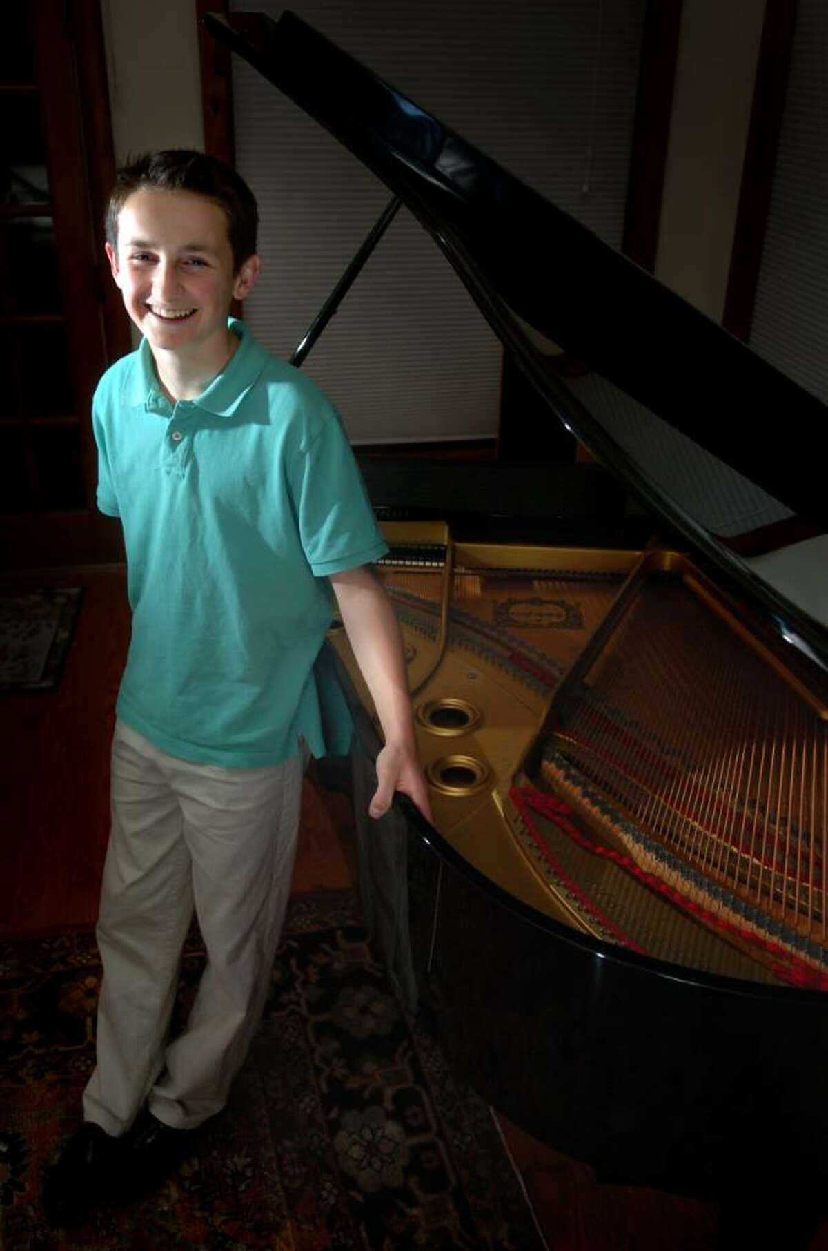 Fifteen-year-old Alex Beyer stands beside his piano in his Fairfield home. The young musician will make his professional debut with the Greater Bridgeport Symphony on Saturday Nov. 14, 2009.