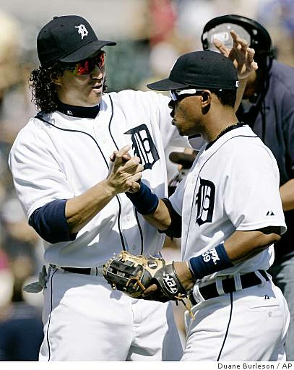 Detroit Tigers' Magglio Ordonez, left, congratulates teammate Ramon Santiago after they defeated the Oakland Athletics 11-7 in a game Sunday, May 17, 2009, in Detroit. Santiago hit a three-run home run and drove in a fourth run in the Tigers' 11-7 win.