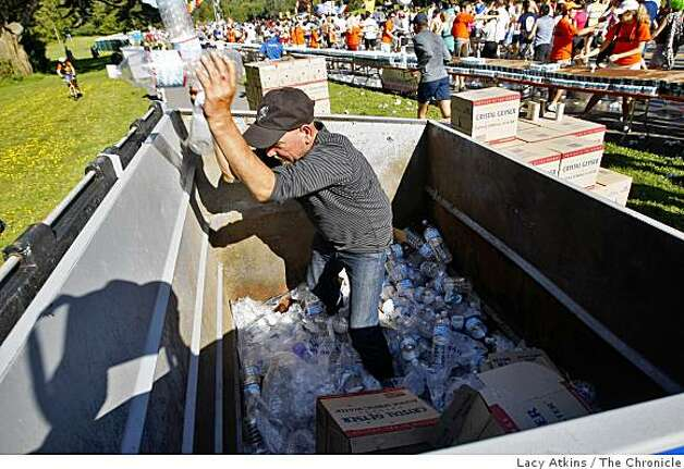 """Chico"" goes through the trash bin collecting plastic bottles to recycle as thousands of people run the Bay to Breakers. Photo: Lacy Atkins, The Chronicle"