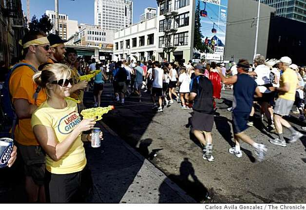 Melissa Lamburt of Sacramento, sprays runners on their way down Howard Street. Photo: Carlos Avila Gonzalez, The Chronicle