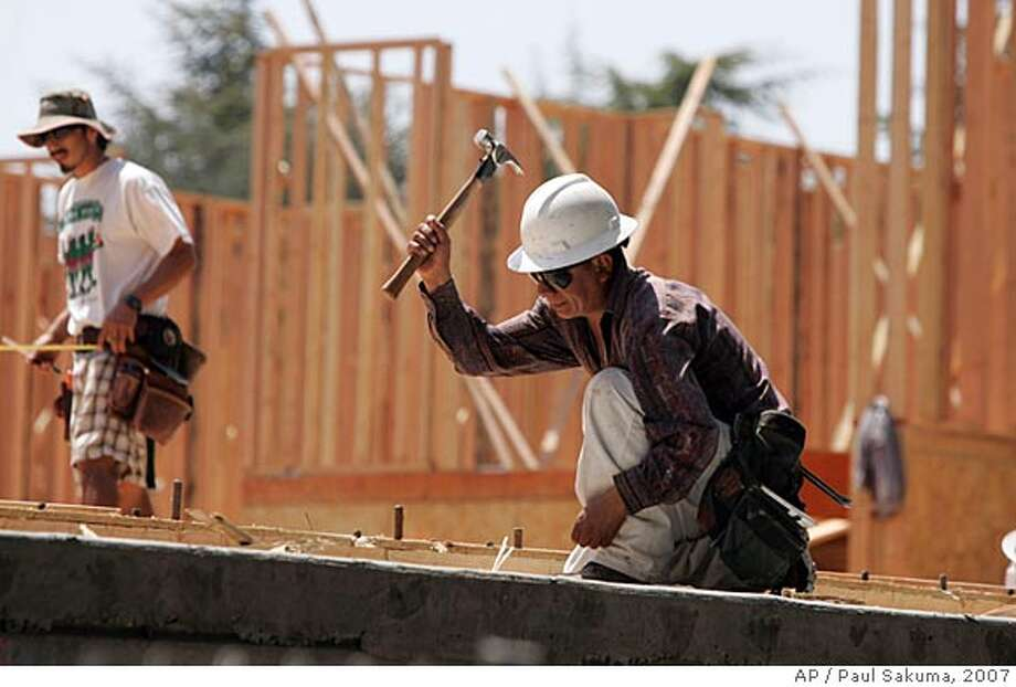 **FILE** Construction workers build a new house in Palo Alto, Calif., in this May 15, 2007 file photo. Employers showed a decent appetite to hire in May, boosting payrolls by 157,000, the most in two months. The unemployment rate held steady at 4.5 percent. The newest report on the nation's overall employment climate, released Friday, June 1, 2007 by the Labor Department, suggested that the sluggish spell the economy has been experiencing hasn't severely crimped companies' need for workers. (AP Photo/Paul Sakuma, file)  Ran on: 06-19-2007  These workers were busy on a Palo Alto house in May, but their job market is expected to slow. MAY 15, 2007 FILE PHOTO Photo: Paul Sakuma