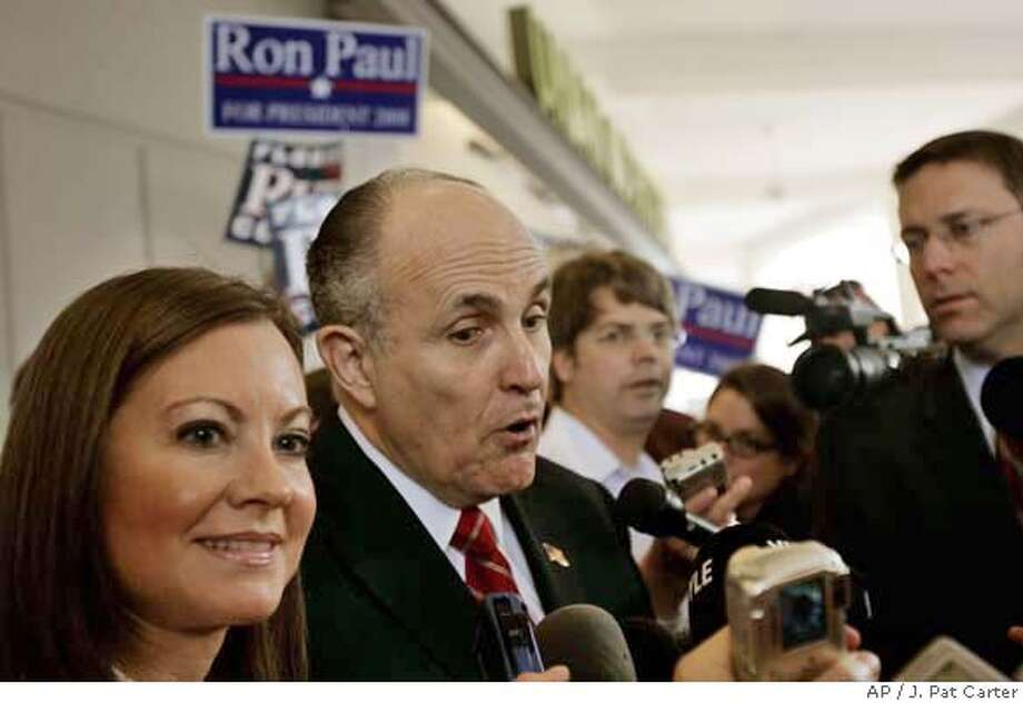 With Ron Paul supporters behind him, Republican presidential hopeful, former New York City Mayor Rudy Giuliani, accompanied his wife Judith, talks to the media and supporters at campaign rally in Palm Beach Gardens, Fla., Tuesday, Jan. 22, 2008. (AP Photo/J. Pat Carter) Photo: J. Pat Carter