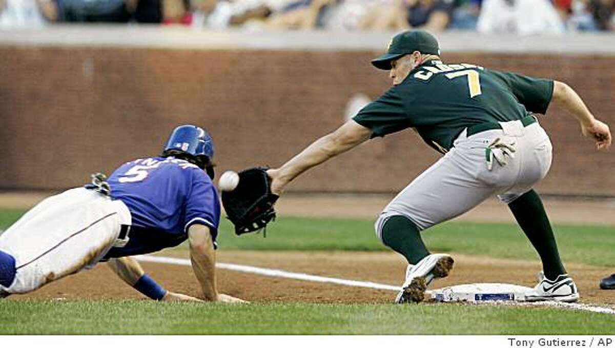 Texas Rangers' Ian Kinsler, left, gets back to first as Oakland Athletics' Bobby Crosby (7) reaches out for the pickoffattempt from starting pitcher Edgar Gonzalez in the first inning of a baseball game in Arlington, Texas, Friday, May 29, 2009. Crosby was unable to handle the errant throw from Gonzalez and Kinsler advanced to second. (AP Photo/Tony Gutierrez)