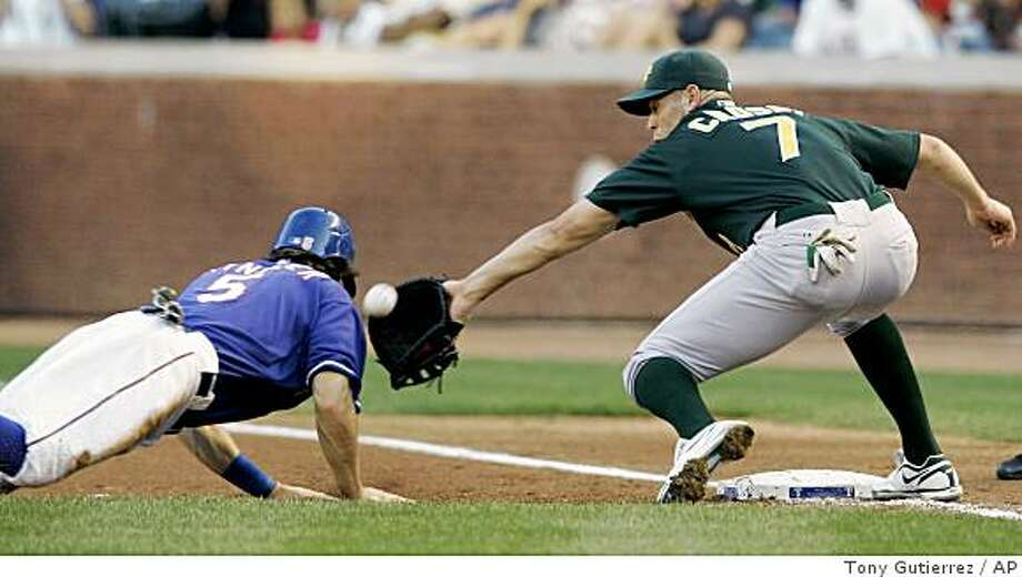 Texas Rangers' Ian Kinsler, left, gets back to first as Oakland Athletics' Bobby Crosby (7) reaches out for the pickoffattempt from starting pitcher Edgar Gonzalez in the first inning of a baseball game in Arlington, Texas, Friday, May 29, 2009. Crosby was unable to handle the errant throw from Gonzalez and Kinsler advanced to second. (AP Photo/Tony Gutierrez) Photo: Tony Gutierrez, AP