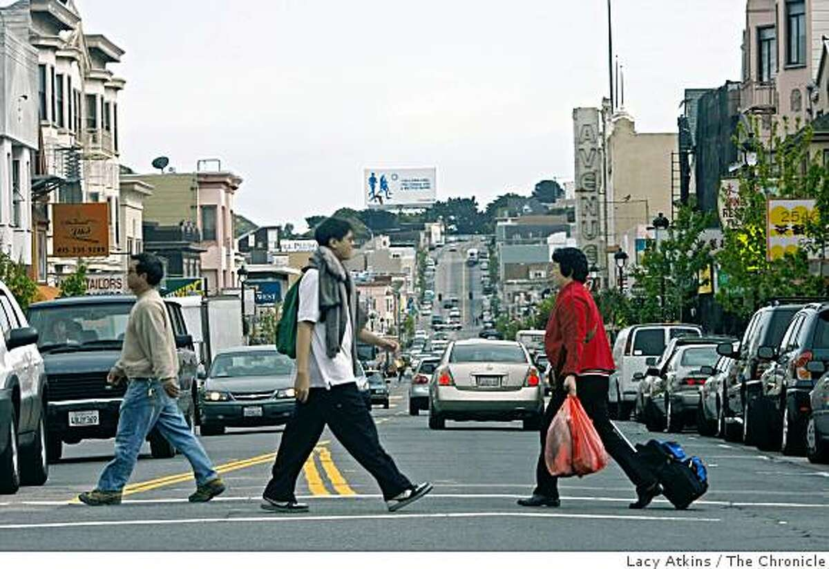 Crowds cross the street after shopping along on San Bruno Ave, in the Portola District, Thursday, April 30, 2009, in San Francisco, Calif.