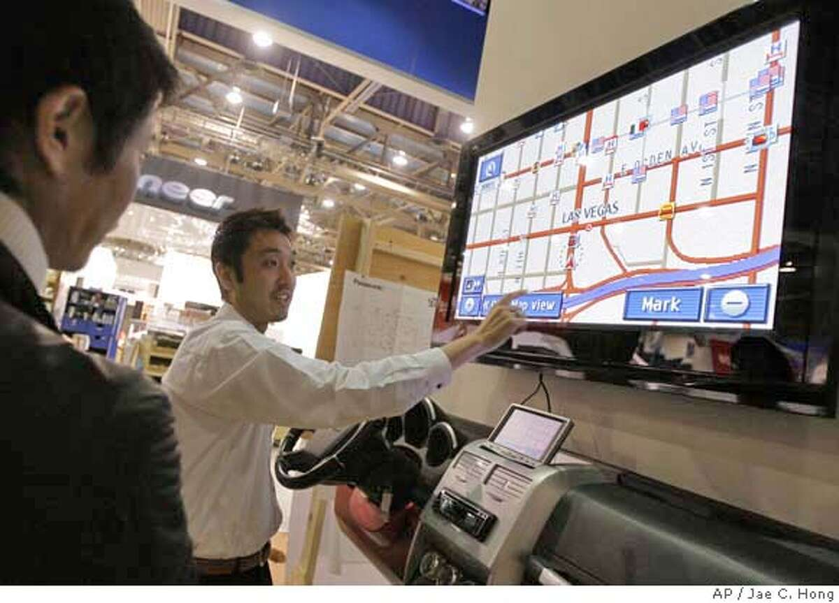 Ken Kimura with Panasonic demonstrates a mobile navigation system at the Panasonic booth at the Las Vegas Convention Center in Las Vegas, Friday, Jan. 4, 2008, as exhibitors get ready for the opening of the Consumer Electronics Show. The CES, the world's largest consumer technology trade show, starts Monday, Jan. 7, in Las Vegas. (AP Photo/Jae C. Hong)