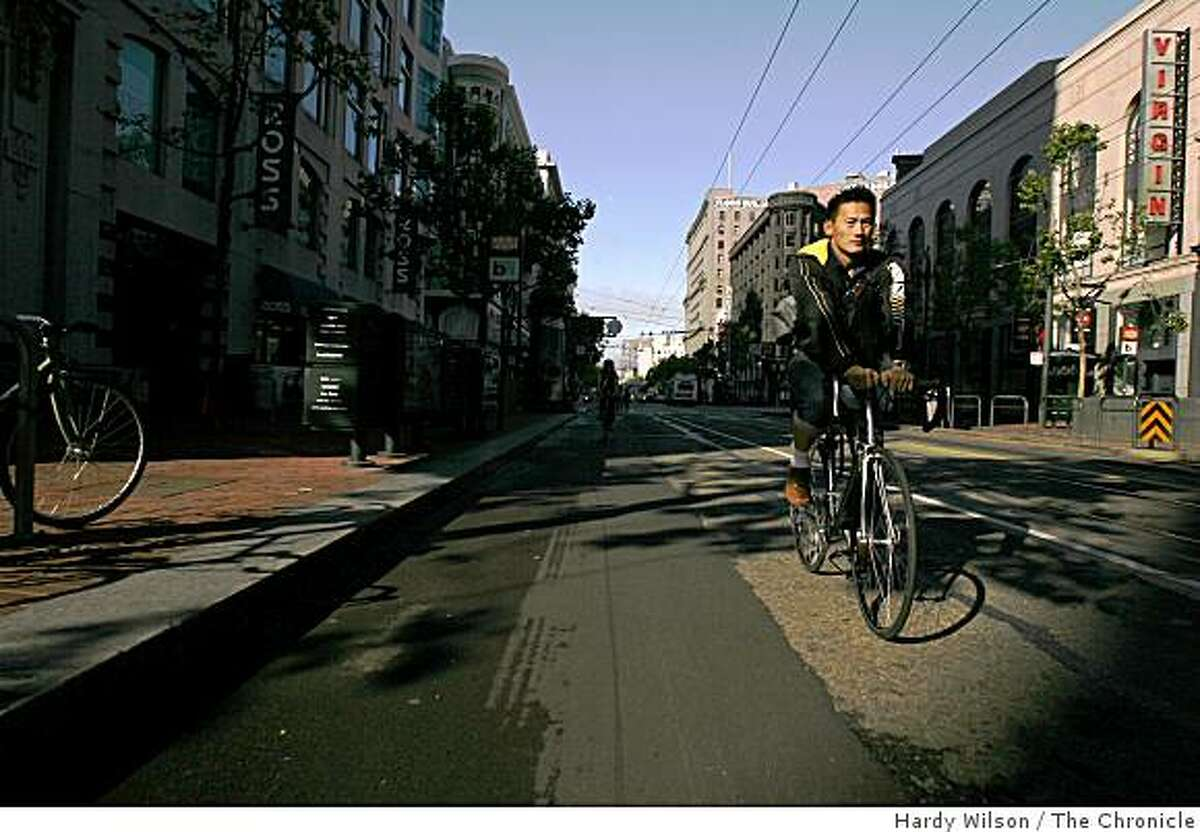 A bicyclist is illuminated by early morning light as he cycles down Market Street during Bike to Work day.