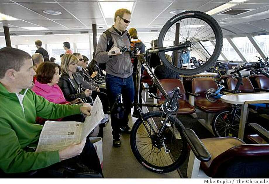Clayton Douglas, of Alameda, loads his bike into the overflow area on the ferry in Oakland during the 15th annual Bay Area Bike to Work day. Photo: Mike Kepka, The Chronicle
