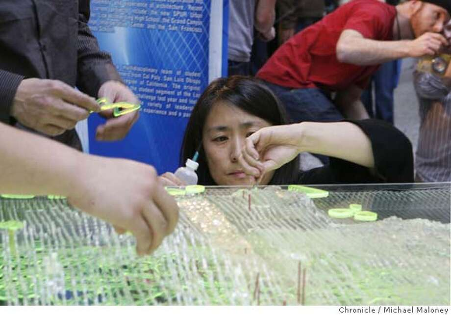 "Lisa Iwamoto of the IwamotoScott Architecture (cq) team glues plastic pieces to her team's project. Eight teams competed in a challenge to design what they envisioned San Francisco would look like in 100 years. Called the ""City of the Future, a Design and Engineering Challenge"", the teams were given 7 days to come up with a concept and only 3 hours to assemble the project at the Ferry Building in San Francisco on Sunday, January 20. 2008. Photo by Michael Maloney / The Chronicle MANDATORY CREDIT FOR PHOTOG AND SAN FRANCISCO CHRONICLE/NO SALES-MAGS OUT Photo: Michael Maloney"