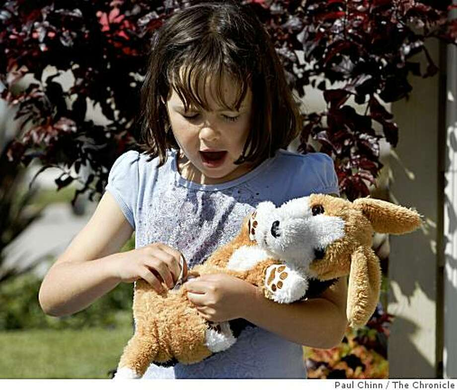 Maya Bliss, 7, cradles a stuffed dog that she claimed at a toy swap organized by the Coastside Mothers Club in Half Moon Bay, Calif., on Saturday, May 16, 2009. Photo: Paul Chinn, The Chronicle
