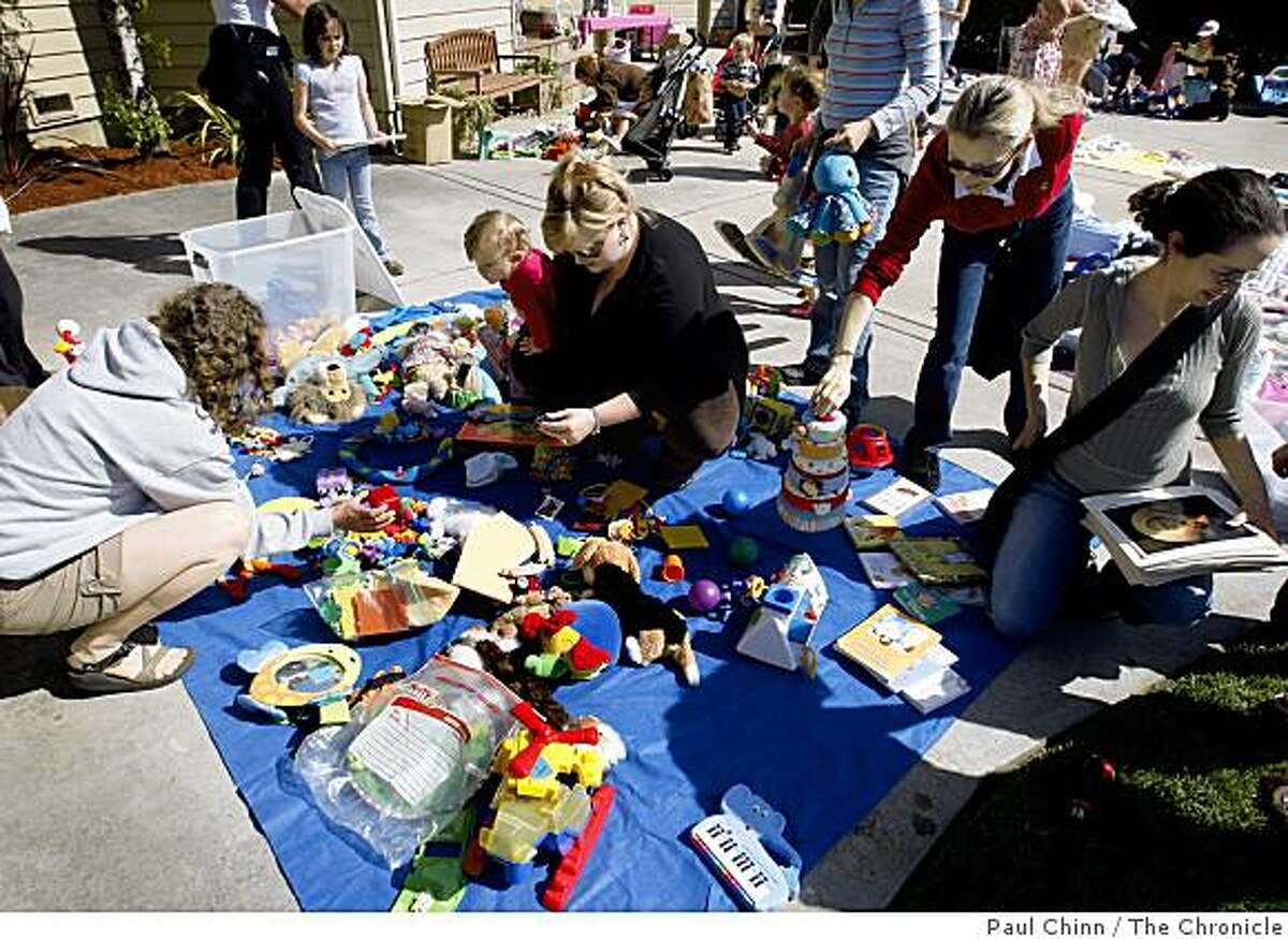 Participants sift through a pile of toys donated for a baby clothes and toy swap organized by the Coastside Mothers Club in Half Moon Bay, Calif., on Saturday, May 16, 2009.