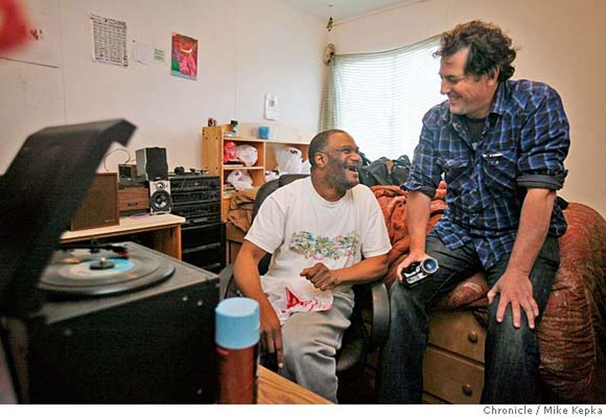 Michael Bernard Loggins and friend Scott Becker listen to newly found 45s on one of Loggins vintage record players. The two are making a film about their friendship called