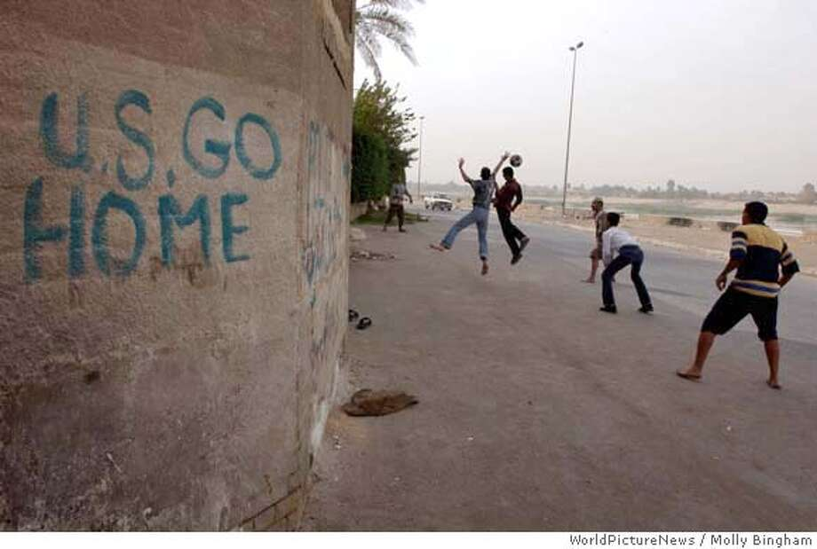 Adhamiya, Baghdad, Iraq -- November 12, 2003.  Photo by Molly Bingham/WorldPictureNews.  The Iraqi resistance to the American occuapation starts at street level, and an attitude of defiance reigns on the alleys and boulevards of Adhamiya. Here, a soccer team trains its goalie against a building's wall inscribed with carefully painted anti-American grafitti, in English. A few weeks later, a pass by the same street that runs along the Tigris River the grafitti had been painted over, presumably by American troops. Photo: Molly Bingham