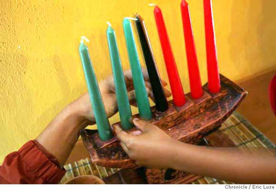 holiday_kwanzaa26_051_el.jpg  Desmond Castillo,7, holds a candle with Shane Hare's hand in the background. Leah Castillo and family celebrate Kwanzaa in their home during the Holidays. Eric Luse / The Chronicle Photo taken on 12/18/07, in San Leandro, CA, USA  Name cq by source  Desmond Castillo  Leah Castillo  Shane Hare MANDATORY CREDIT FOR PHOTOG AND SAN FRANCISCO CHRONICLE/NO SALES-MAGS OUT Photo: Eric Luse
