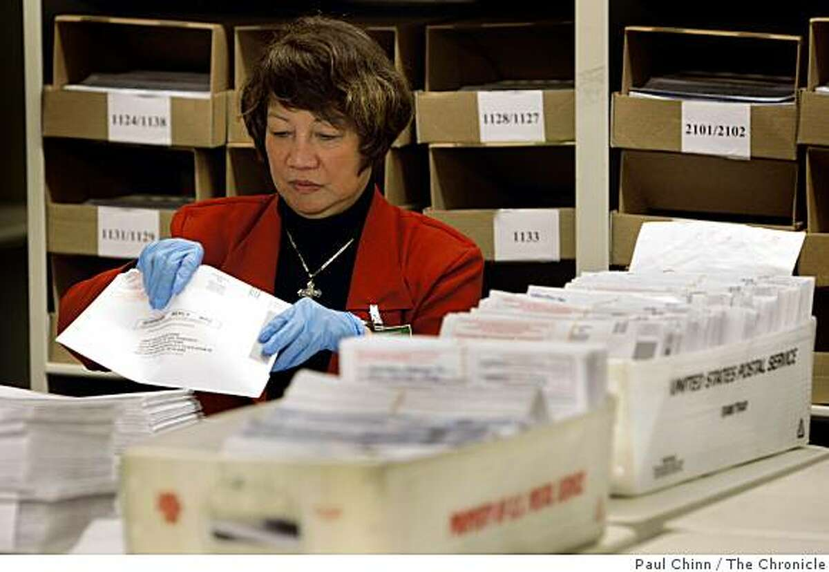 Milagrosa Caguioa inspects absentee ballots before they're counted in the basement of City Hall in San Francisco, Calif., on Tuesday, May 19, 2009.