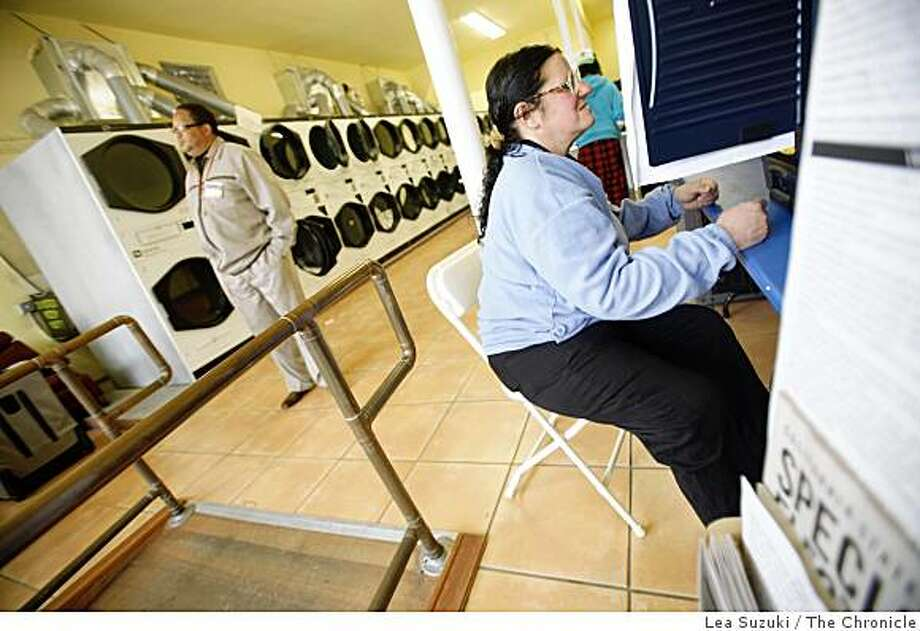 Monique Koller uses a voting machine at Get the Funk Out laundromat in San Francisco as polling inspector Don Phillips looks over the polling station. Photo: Lea Suzuki, The Chronicle