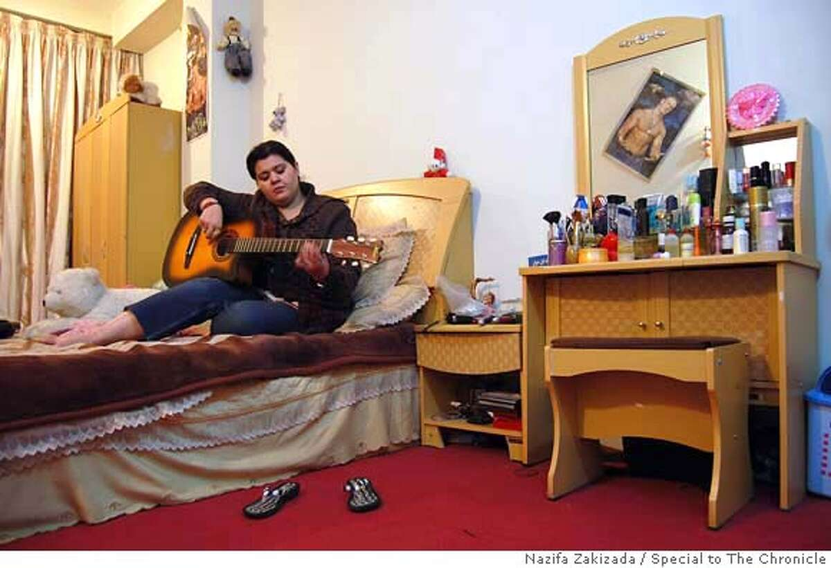 afghanXX_music_02.JPG Farida Tarana, 24, in her bedroom in Kabul plays with the instruments she has recently learned to play. Tarana attends a secret music school for women where she takes voice and guitar lessons. Nazifa Zakizada / Special to The Chronicle MANDATORY CREDIT FOR PHOTOG AND SAN FRANCISCO CHRONICLE/NO SALES-MAGS OUT