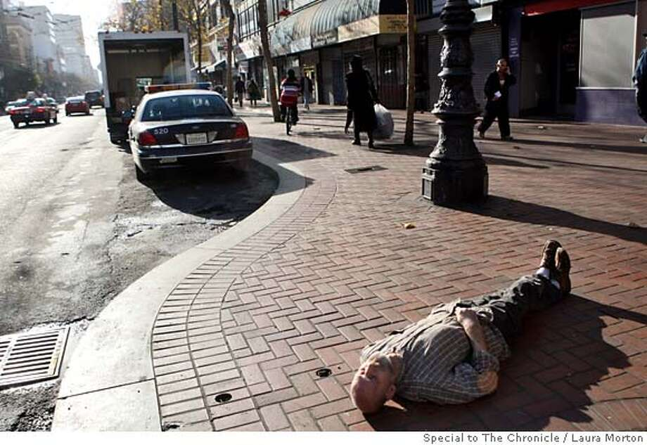 Nevius16_0005_LKM.jpg A man naps on the Market St. sidewalk on Friday afternoon. A recent sidewalk access ordinance in Portland, OR prohibits people from sitting on the sidewalk in high traffic areas during certain times and gives them alternative places to go. (Laura Morton/Special to the Chronicle) EDITOR'S NOTE: Man did not refuse to give his name, but his response was too incoherent to be certain on correct name Photo: Laura Morton