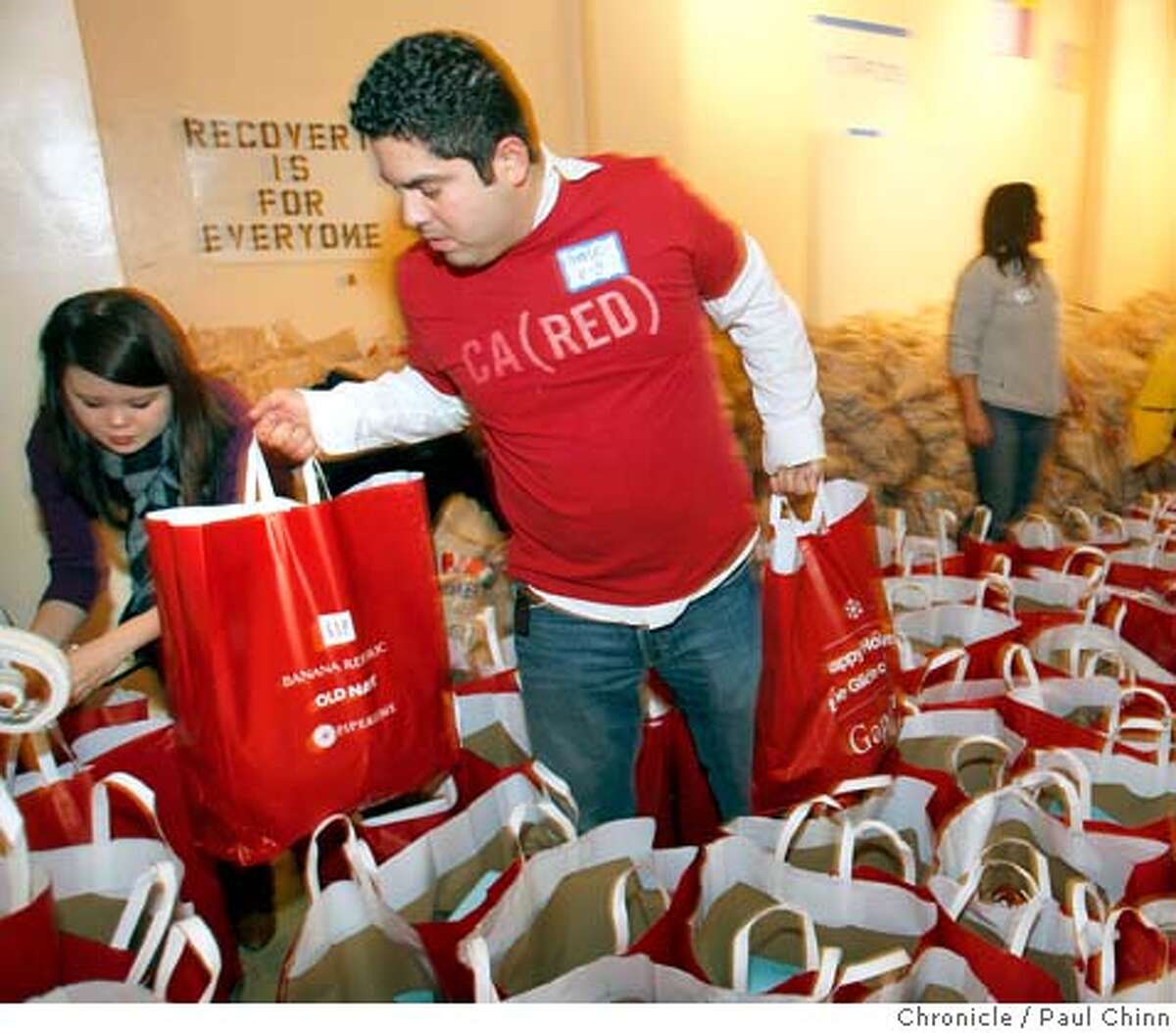 Volunteer Charlie Zammit moves bags forward during the annual grocery bag giveaway for those in need at Glide Memorial Church in San Francisco, Calif. on Wednesday, Dec. 19, 2007. Each of the 6,000 bags contained either a turkey or a chicken, potatoes, bread, pasta and vegetables. Some of the recipients were in line as early as 9 p.m. Tuesday. PAUL CHINN/The Chronicle **Charlie Zammit