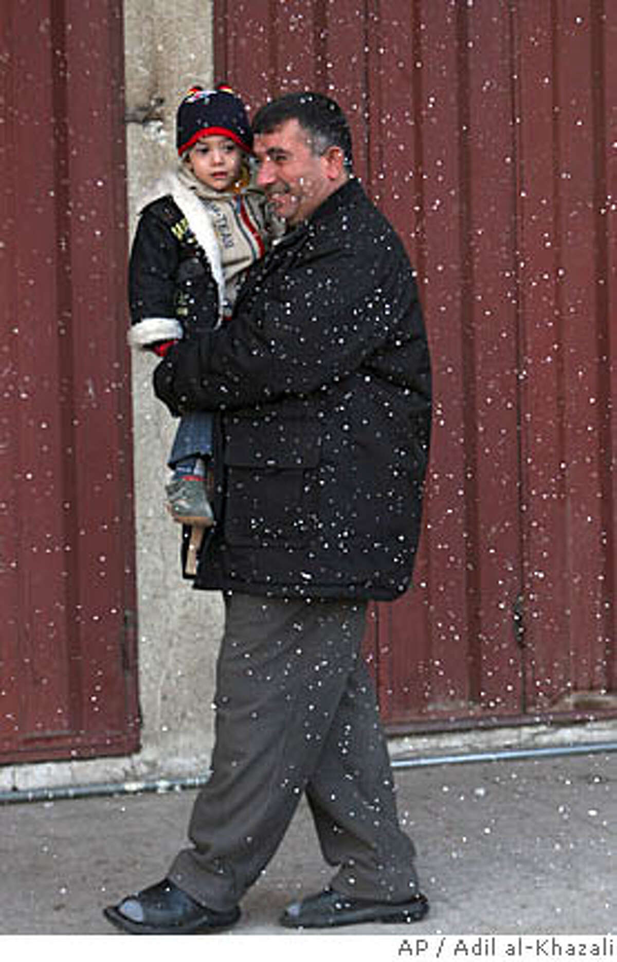 An Iraqi man and his child enjoy light snow fall in eastern Baghdad, Iraq on Friday, Jan. 11, 2008. After weathering nearly five years of war, Baghdad residents thought they'd pretty much seen it all. But Friday morning, as muezzins were calling the faithful to prayer, the people here awoke to something certifiably new. For the first time in memory, snow fell across Baghdad.(AP Photo/ Adil al-Khazali)