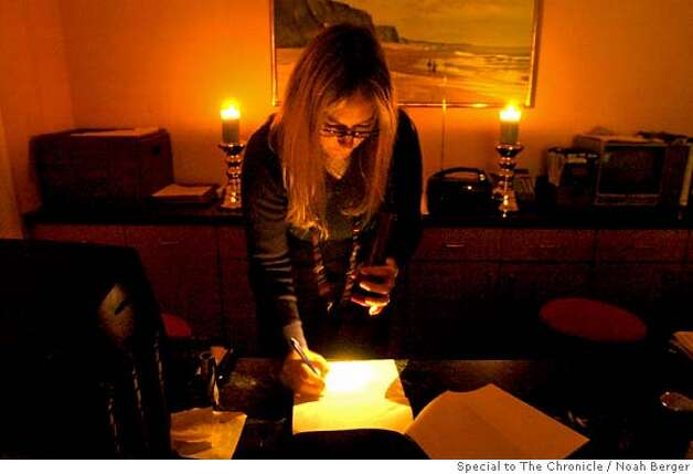Dana Dahl, general manager of the Beach House in Half Moon Bay uses candles and a flashlight to run the hotel�s front desk on Friday, Jan. 4, 2007. Although the hotel�s heat is not working, each room has a fireplace to keep guests warm through the end of the storm. (Photo by Noah Berger) Photo: Noah Berger