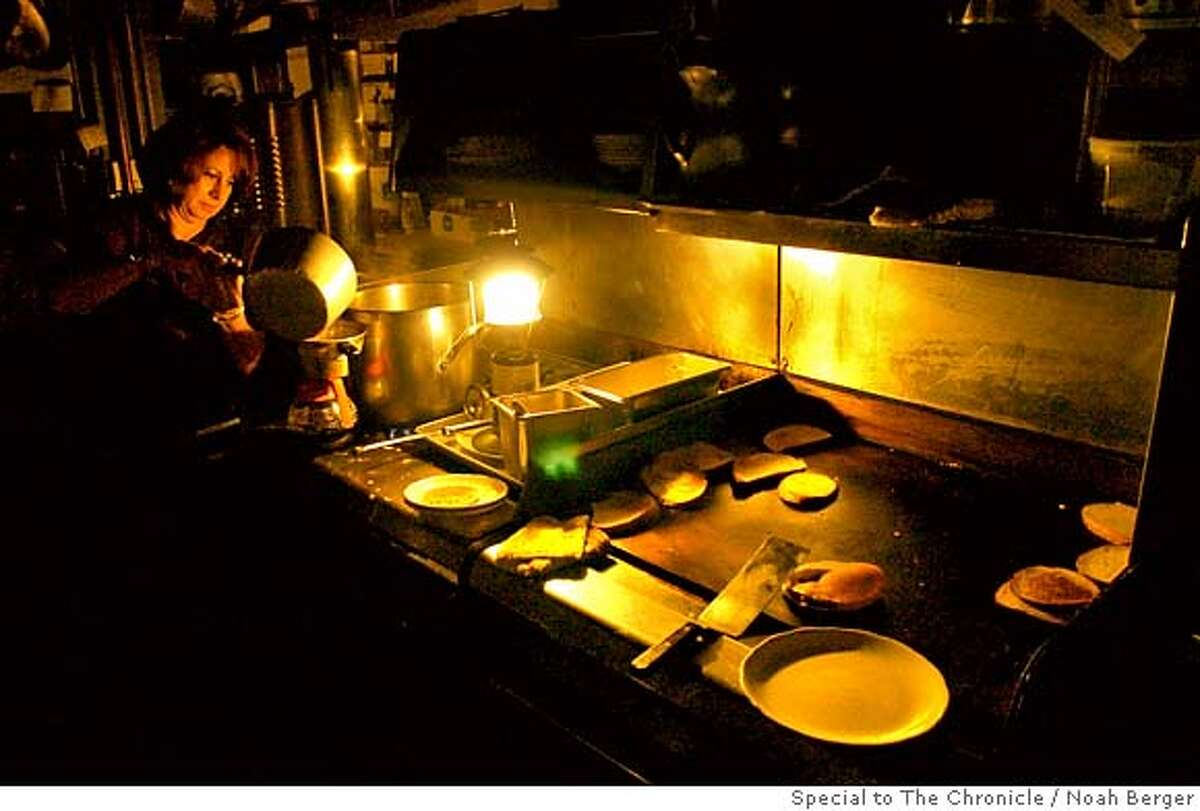 An employee at Nick�s Restaurant in Pacifica makes coffee using the light from a propane lantern on Saturday, Jan. 5, 2008. Like much of the city, Nick�s operated without power Saturday as heavy rains and wind continued to pound the coast. Earlier in day, waves breached a nearby breakwater sending water through the restaurant�s front door. BY NOAH BERGER/SPECIAL TO THE CHRONICLE